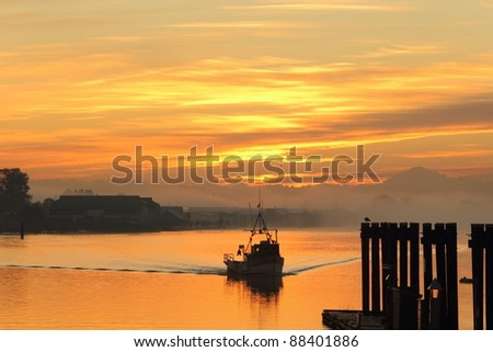 A fish boat departs Steveston Harbor on the Fraser River in British Columbia, Canada during a misty sunrise.