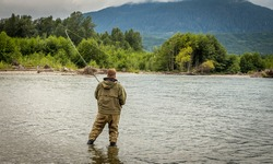 A fisherman battling a salmon while wading on the Kitimat River in British Columbia, Canada, with the rod bent and forest and mountains in the background
