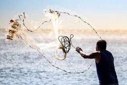 A fisherman casting a net into the water during on a golden horizon