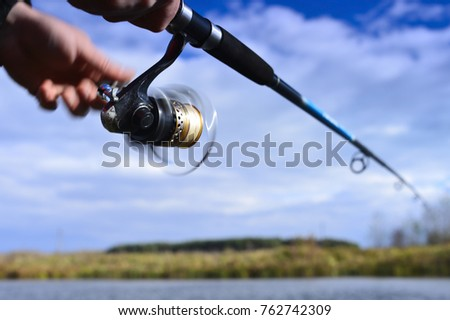 A fisherman catches a fish. Spinning reel closeup. Blurry #762742309