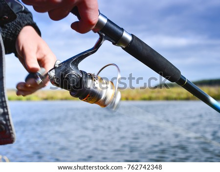 A fisherman catches a fish. Spinning reel closeup. Shallow depth of field on the spool of fishing line. #762742348