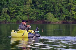 A fisherman fight against a pike. The man is sitting in the fishing inflatable boat and he use flippers to move on the water. He also use a sonar (fish finder) to detect the fish underwater
