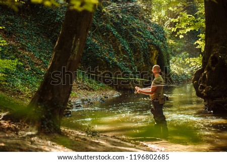 A fisherman fishing with fly fishing in the flowing stream