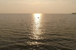 A fisherman in a boat in the sea against the sunset.