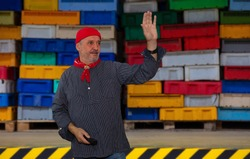 A fisherman in front of a hall where fish are traded. The man wears a typical North German fisherman's shirt with a red bandana. In the background are boxes for the transport of fish.