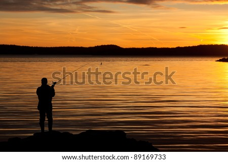 A fisherman in sunset at the coast. - stock photo
