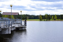 A fisherman is fishing on a lake from a concrete pier.