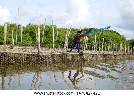 A fisherman is throwing a Cast Net