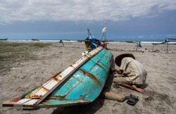 A fisherman mends his boat on the beach at the beach in West Sumatera Indonesia.