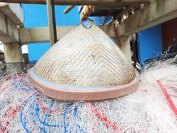 A fisherman's bamboo-woven hat on a pile of fishing nets. These items are some of the fishing equipment for work.