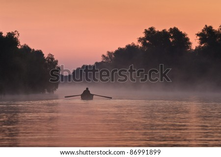 a fisherman's boat in the morning fog