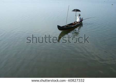 A fisherman sitting on a boat  fishing in a lake
