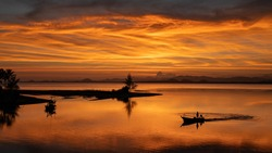 A fisherman stands on a boat to fish in the sea, a beautiful silhouette background to the sunset.