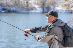 A fisherman with a fishing rod and a backpack catches fish on the bank of a snow-covered river in early spring.