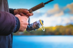 A fisherman with a fishing rod. Close-up of a hand holding a spinning rod and twisting a coil. Colorful view, blurred background, selective focus.