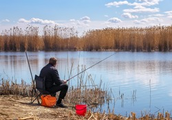 A fisherman with a fishing rod sitting on a chair on the river bank. The concept of a rural getaway.