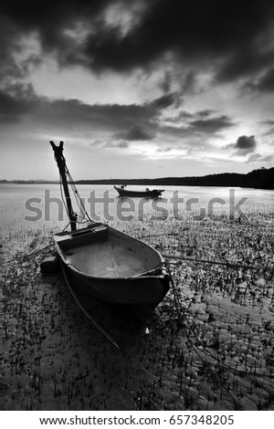 A fishermen boat grounded during a low tide. Pictured in a black and white.