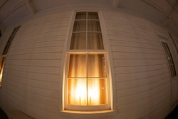 A fisheye view of the exterior of a home with candles lit in a window