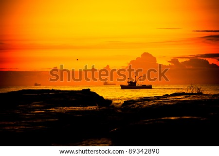 A fishing boat cruises by the shore at dawn in Wollongong, New South Wales, Australia