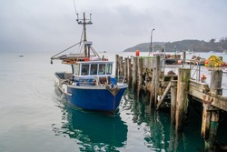 A fishing boat docks at the wharf, floats on the still sea, waiting for the next trip out on the ocean, Stewart Island, New Zealand