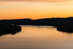 A fishing boat drifts peacefully as golden light reflects on a lake at sunset in northern Minnesota.