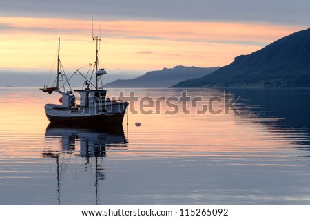 a fishing boat lies at sundown in the fjord