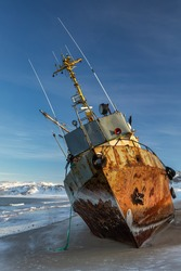 A fishing boat lying on its side, washed up by a storm on the shore of the Barents sea, the Kola Peninsula, Teriberka, Russia