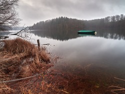 A fishing boat moored on a calm lake on a cloudy morning. The dreamy landscape of the German Neyetalsperre lake in the city of Wipperfurth. A small boat covered with a green tarpaulin.