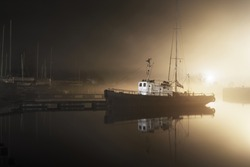A fishing boat moored to a pier in a fog at night. Sailboats in the background. Yacht club illuminated by lanterns. Reflections on the water. Daugava river, Riga, Latvia