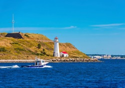 A Fishing Boat Past a Small Lighthouse and Shed in Halifax, Nova Scotia, Canada
