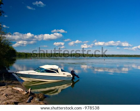 A fishing boat waits ashore on a clear sunny day at the lake.
