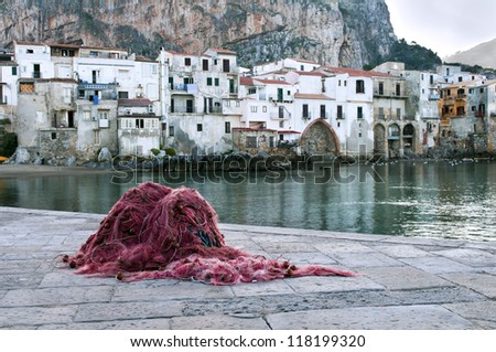 A fishing net and the old town of Cefalu, Sicily
