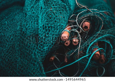 A fishing net is a net used for fishing. Nets are devices made from fibers woven in a grid-like structure. Some fishing nets are also called fish traps, for example fyke nets.