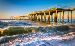 A fishing pier and waves in the Atlantic Ocean at sunrise, in Ventnor City, New Jersey.