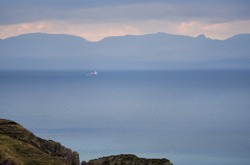 A fishing trawler out catching fish on Loch Gairloach as a rain shower comes in from the Torridon mountains in the Scottish