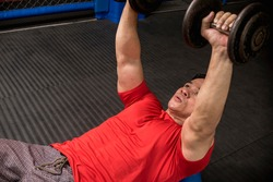 A fit and athletic asian guy does dumbbell presses on a stability ball. Chest workout at the gym.