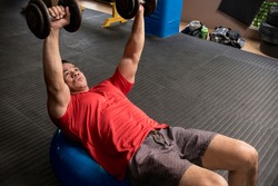 A fit and athletic asian guy does Stability Ball Dumbbell Chest Press. Working out at the gym or fitness center.