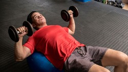A fit and handsome asian guy does Stability Ball Dumbbell Chest Press. Active lifestyle, at the gym or fitness center.