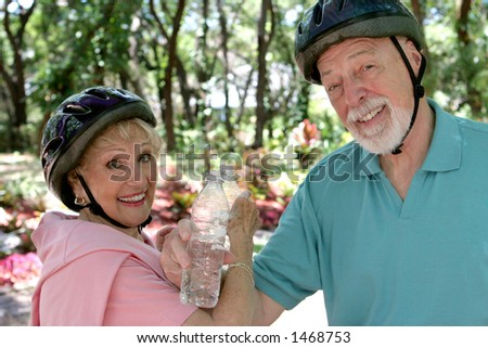 A fit senior couple cooling off with water after riding their bikes.
