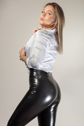 A fit woman wearing a white loose shirt and black leather pants looking seductively at the camera