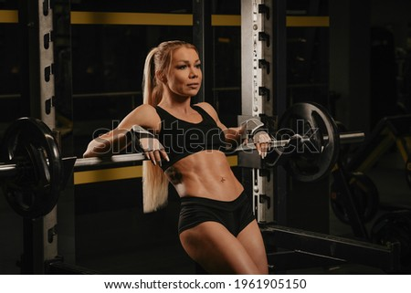 A fit woman with long blonde hair is laying on a barbell at the squat rack in a gym. A girl is relaxing after a workout. Foto stock ©