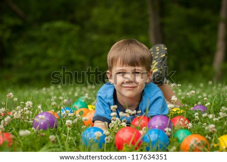 A five year old boy lays in the grass surrounded by colorful toy balls. The boy has expressions of fun and happiness.