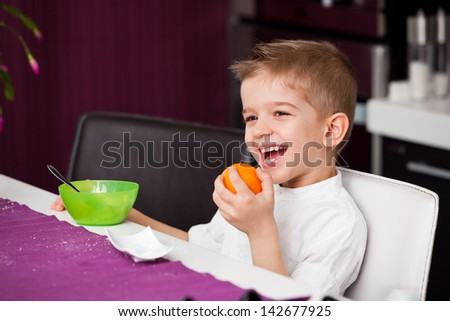 A five year old boy sitting at a kitchen table with an orange in his hand and a bowl in front of him. A five year old boy having breakfast