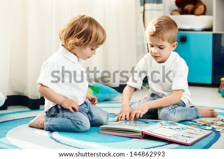 A five year old child and his two year old brother playing in their room. A five year old child showing his two year old brother the pictures from a book