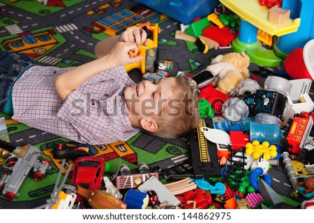 A five year old child playing in his room with a lot of toys around him