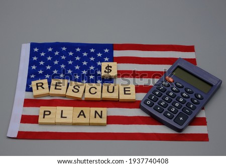 A flag of the United States of America with a dollar sign and a wooden inscription, rescue plan,with a calculator nearby. Concept of economic stimulus, against the recession  Stock photo ©