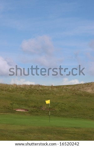 a flag waving on a hole on a golf course in ireland