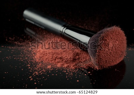 a flat blush brush with pink blush on it, placed on some loose powder blush, shot on black backgrownd.