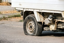 A flat car tire on the road Leaking because of the damaged wheel nails, old, dirty, cannot be used Damaged wheels on the road