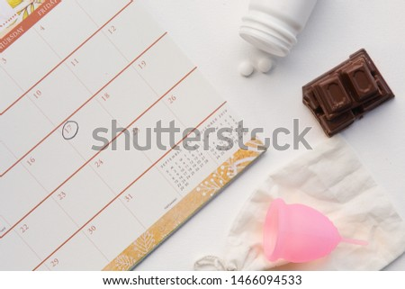 A flat-lay of items useful for a woman's period - a calendar with a date circled, menstrual cup, pain killers and chocolate